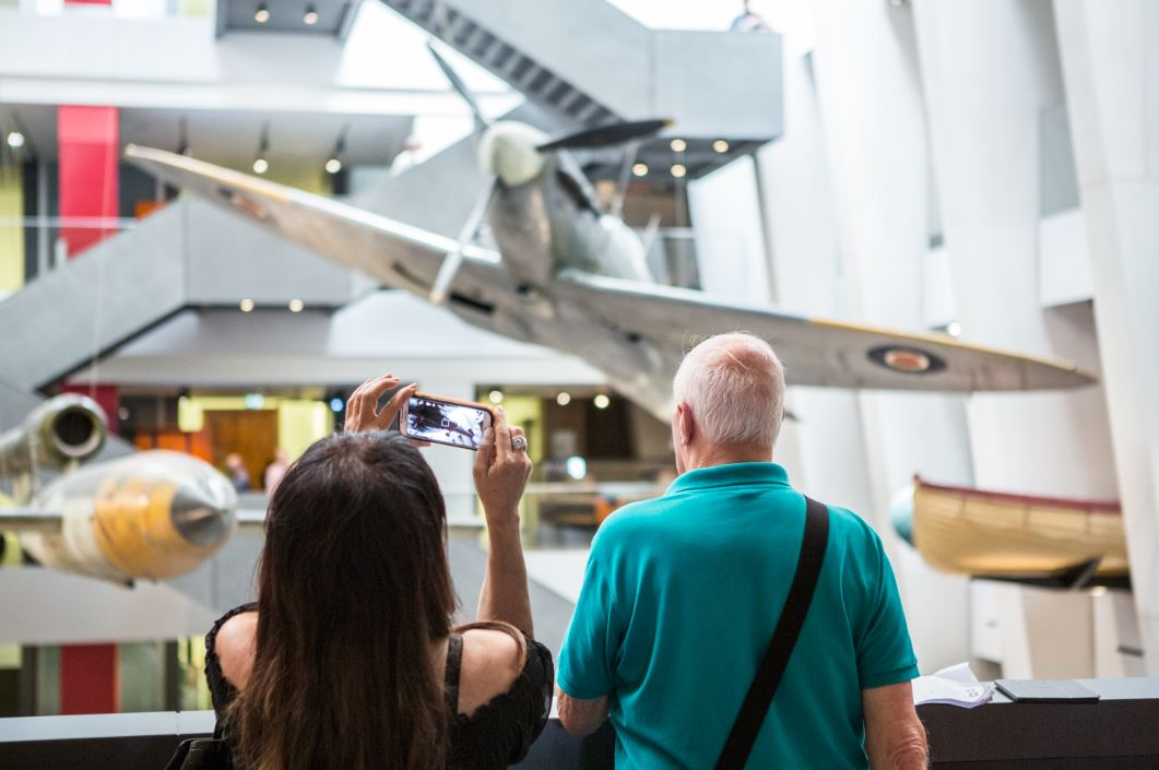 Visitors viewing the 'Witnesses to War' objects in the IWM London atrium