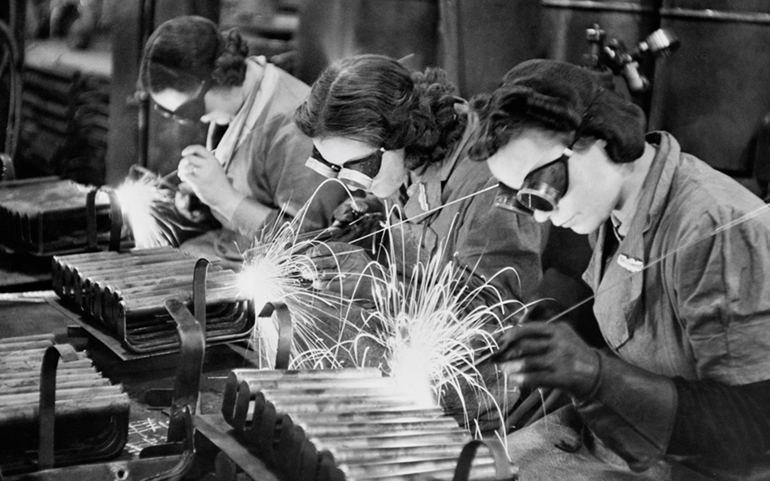 A photograph showing women welders making stirrup pump handles during the Second World War.