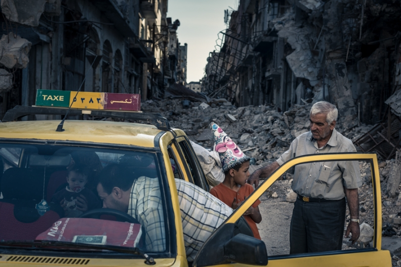Abu Hisham Abdel Karim and his family use a local taxi to salvage possessions from their ruined apartment in the Khalidiya district of Homs.