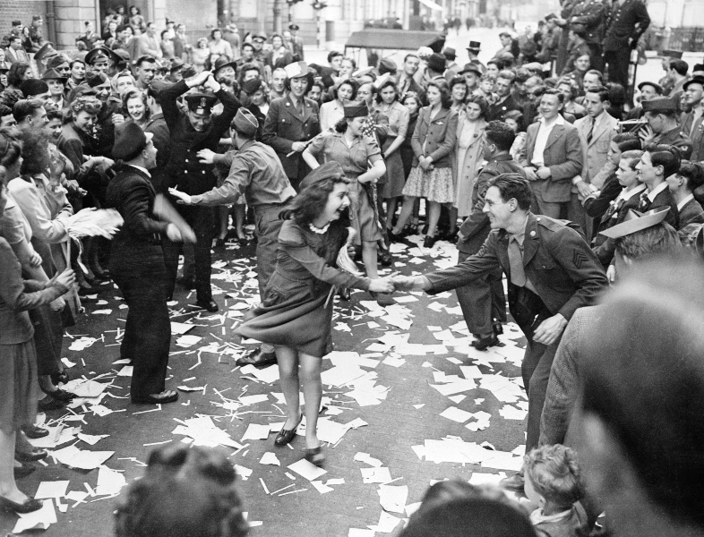 "British girls, of the Picture Division of the London Office of War Information dance in the street with American soldiers during the ""VE Day"" celebration in London May 8, 1945."