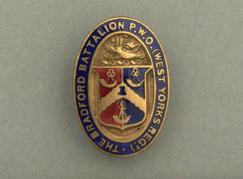 metal oval button-hole badge bearing the Arms of City of Bradford in gilt, red and blue enamel with the inscription in gold around the blue enamelled edge: 'THE BRADFORD BATTALION P. W. O. (WEST YORKS REGT.)'.