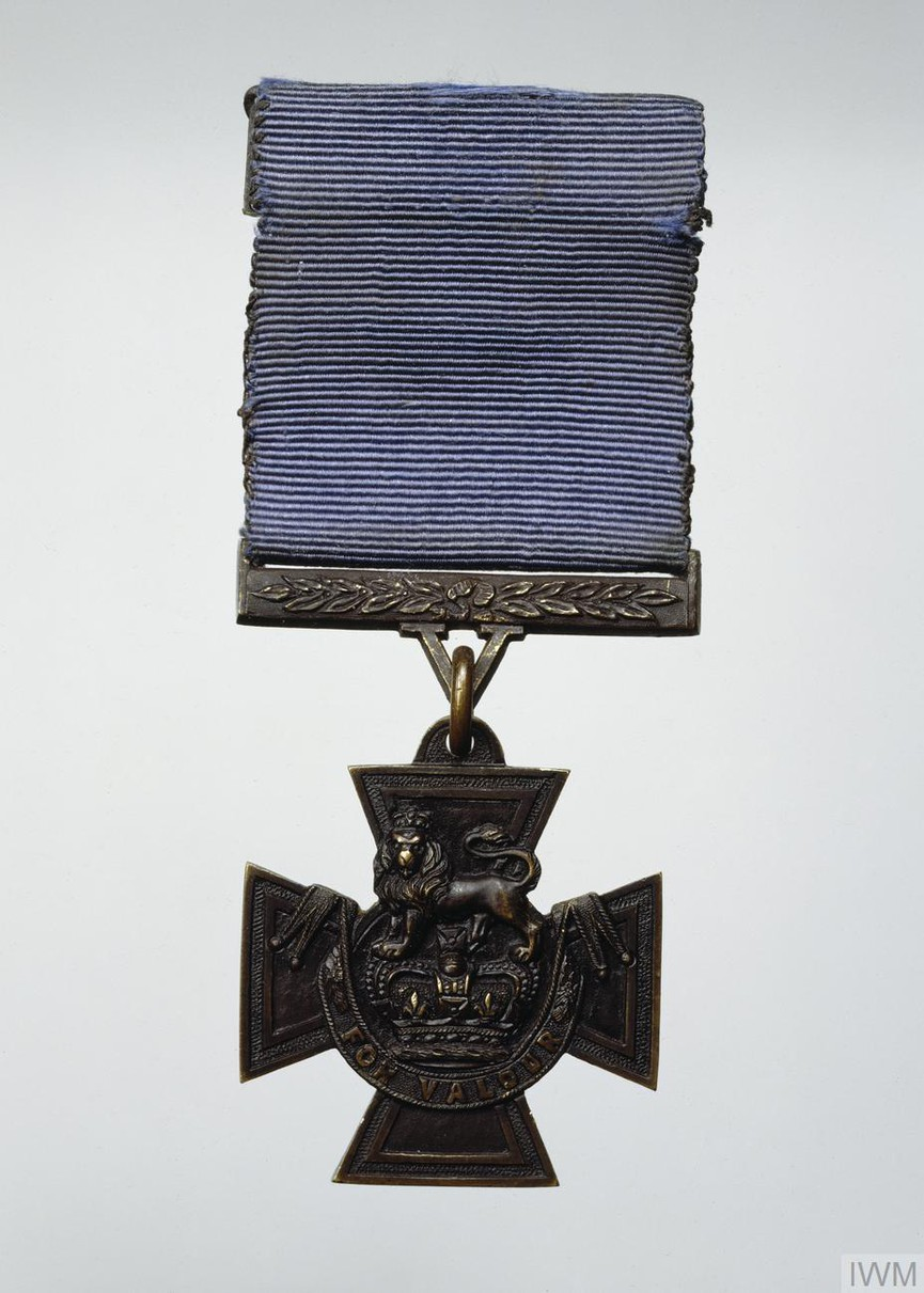 cross patté (described in the Royal Warrant as a 'Maltese cross of bronze') having at its centre a crown surmounted by 'lion gardant'; beneath the crown an ornamentally draped scroll bearing the motto: 'FOR VALOUR'. Raised borders outline the shape of the cross. The plain reverse bears a central circle (with raised edge) to enclose the date of the act of gallantry. The suspension bar comprises a straight laurelled bar with integral 'V' lug