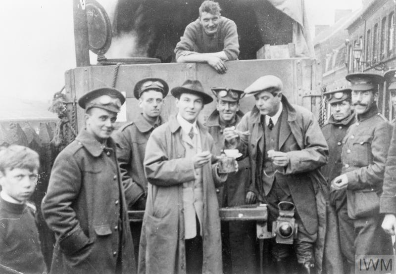 Journalists share a meal with troops at a roadside mobile army kitchen on the Western Front in October 1914.