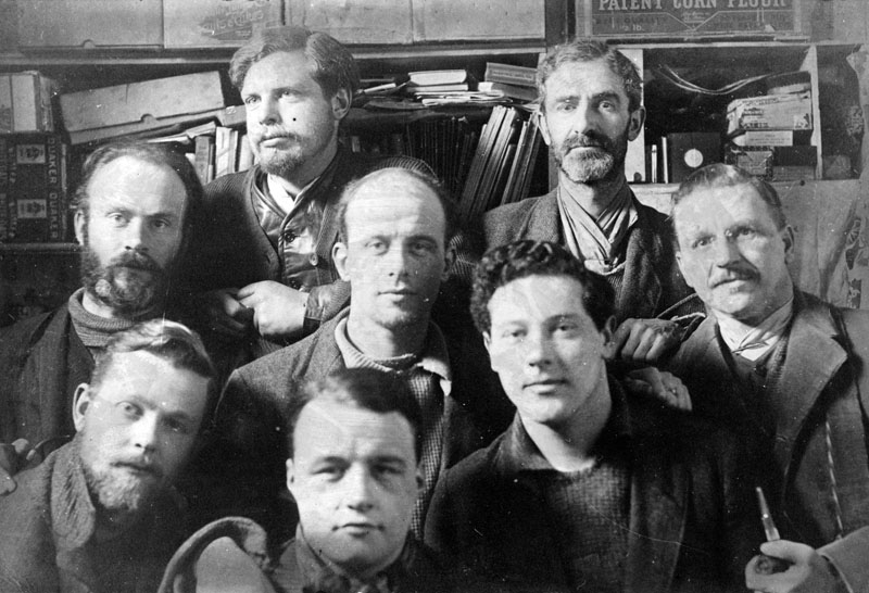 A group of eight prisoners pose for the camera at Ruhleben camp. The man on the right has a pipe in his hand.