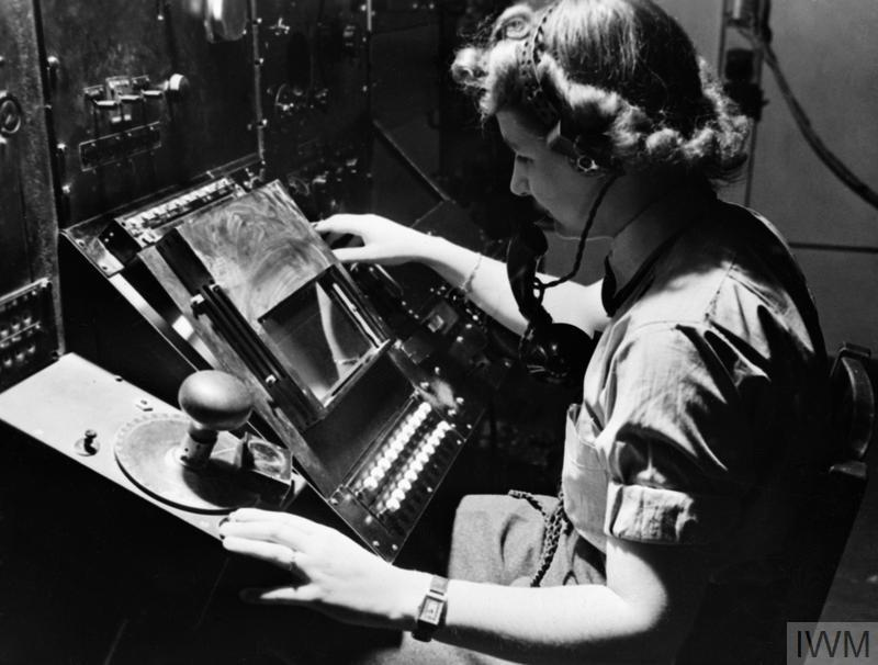 WAAF radar operator Denise Miley plotting aircraft on the CRT (cathode ray tube) of an RF7 Receiver in the Receiver Room at Bawdsey CH. Her right hand has selected the direction or heightfinding and her left hand is ready to register the goniometer setting to the calculator.