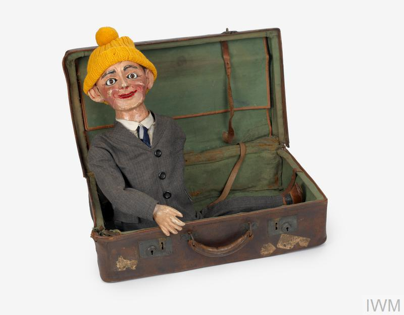 dummy, case and framed service postcard ventriloquist's dummy in rectangular brown leather suitcase, the dummy has painted papier mache hands and head and is wearing a grey fabric suit with brown leather shoes. Note the hole in the case which was made by shrapnel from a German artillery shell.