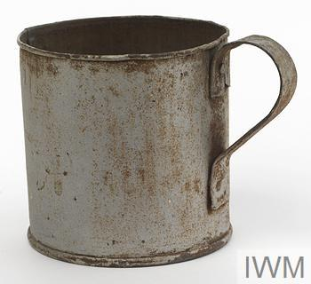 Mug made from a condensed food tin. A handle is attached with two rivets to the side of the tin opposite the seam and the outer surface a painted a silver colour.