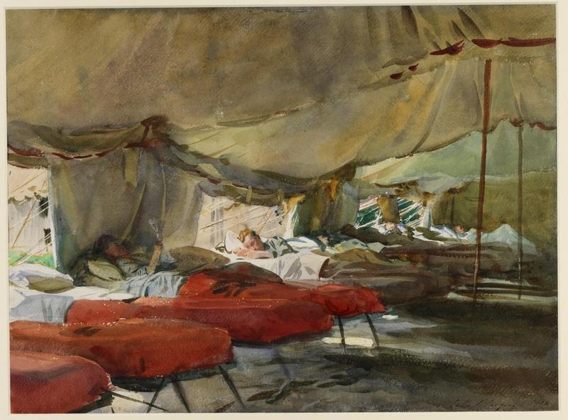 the interior of a hospital tent with campbeds lining the side. Many of the beds are occupied and covered with brown or red blankets. One soldier lies propped up on pillows reading, another sleeps turned on his side the light from the open tent flap falling on his bed.