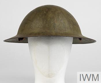 Helmet: bowl-shaped steel helmet, painted in a textured matte olive colour and has a hand-applied insignia to the left side featuring a stylised plume in yellow. The helmet has a steel rim, lapped and welded at the rear. Inside only the asbestos pad to the crown and the oilskin (or American cloth) headband is present, the padded cloth crownpiece missing. Only 90% of the leather chinstrap is present.