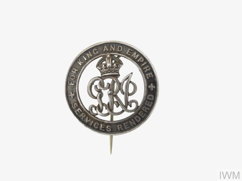 circular silver open-work lapel badge comprising the ornate Royal cypher 'GRI' surmounted by a crown and enclosed by a circular edged band bearing the embossed text: 'FOR KING AND COUNTRY' and 'SERVICES RENDERED'. The reverse bears the unique serial number 'B186968'.