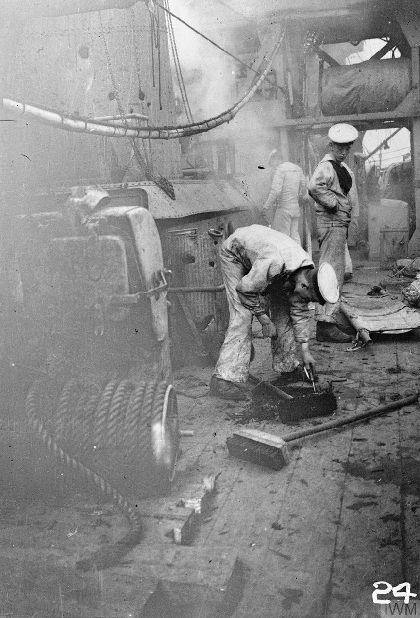 Damage to the deck of HMS CHESTER sustained during the battle of Jutland. Several sailors can be seen on deck including one bending down to inspect the hole. Boy (1st Class) Jack Travers Cornwell was posthumously awarded the Victoria Cross for remaining at the forward gun on board the cruiser. The ship was badly shelled by four German cruisers and Cornwell's position was hit four times, killing all the crew apart from Cornwell.