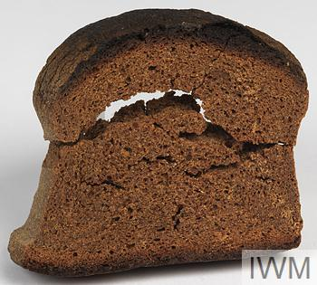 thick slice of black bread which has (over time) crumbled into three pieces.