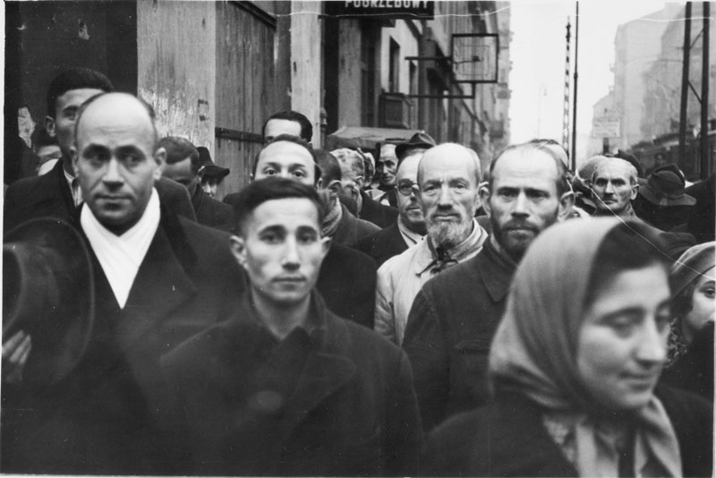 "Jewish pedestrians standing on a street in the getto, probably at the intersection of Żelazna and Chłodna (Grubenstrasse) Streets. Note that all men removed their hats in the presence of the German photographer. There is a funeral home in the background - ""Zakład pogrzebowy""."