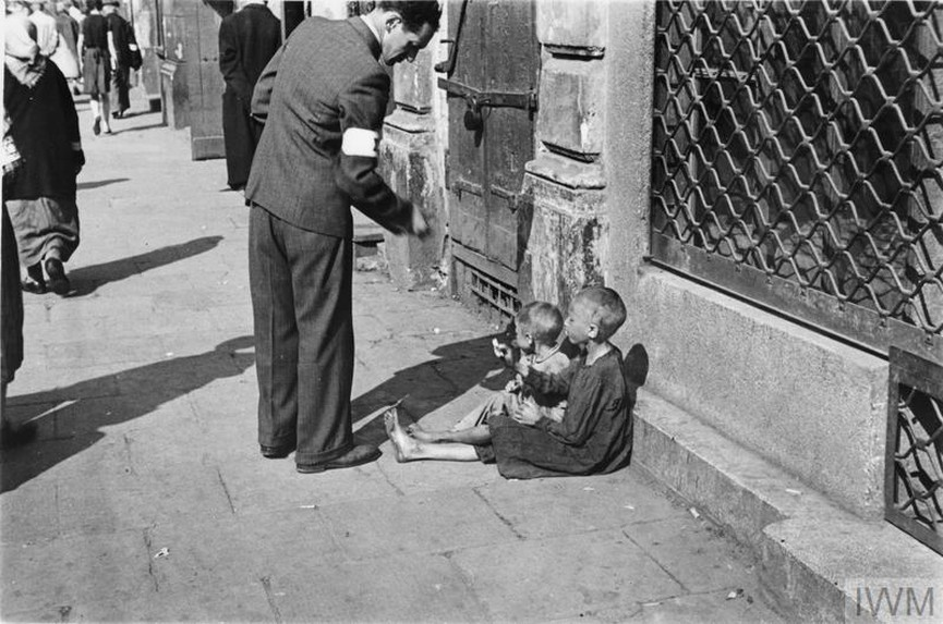 A passer-by giving money to two destitute children on the street in the ghetto.