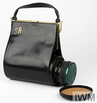 Respirator and carrier: standard civilian pattern respirator with a black rubber mask and metal filter contained within the base of a black leather lady's clutch handbag.