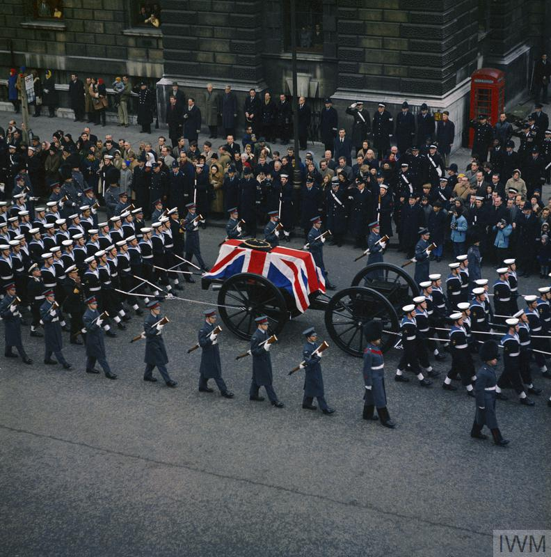 The state funeral of Sir Winston Churchill KG. The coffin, bourne on a gun carriage is pulled by a detachment from the Royal Navy and escorted by members of the RAF and guards regiments, with arms reversed. The cortege moves up Whitehall, London and passes the entrance to Downing Street heading towards Trafalgar Square. Crowds line the street to pay their respects. The coffin is draped with the Union Flag and carries the insignia of a Knight of the Garter.