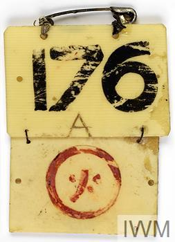 "A rectangular piece of yellowing plastic with the number ""176"" painted on it and the letter ""A"" scratched into it. Suspended from this by a piece of twisted wire is a second piece of plastic with a red Japanese character inside a red circle painted on it. Tied to the top of the tag is a large safety pin."