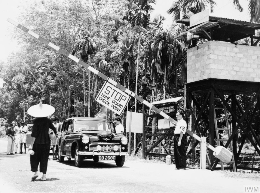 A member of the Malayan Home Guard mans a check point on the edge of a town. Such check points allowed the authorities to search vehicles and intercept food and supplies being smuggled out to the communist terrorists.