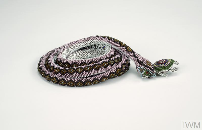 A coiled snake covered with pink, white, amber, blue, black and brown beads. In its mouth a beaded mouse-like animal of green, orange, purple, white, pink and red beads.