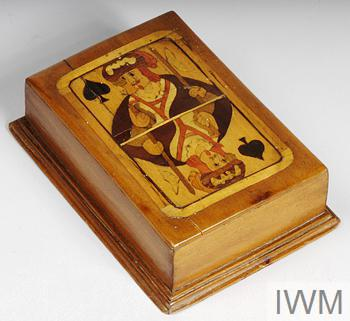 Card box with marquetry on lid depicting the King of Spades, the inside is lined with purple cloth and is complete with the following inscription written in ink: MADE AT PRISONERS OF WAR CAMP CATTERICK.