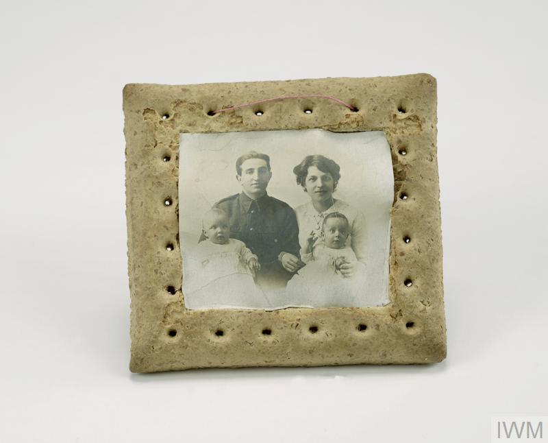 Square hard tack 'army biscuit' with central section recessed to accommodate a family portrait photograph, a length of pink cotton thread is threaded through two of the perforations at the top of the biscuit to hang the 'picture'.