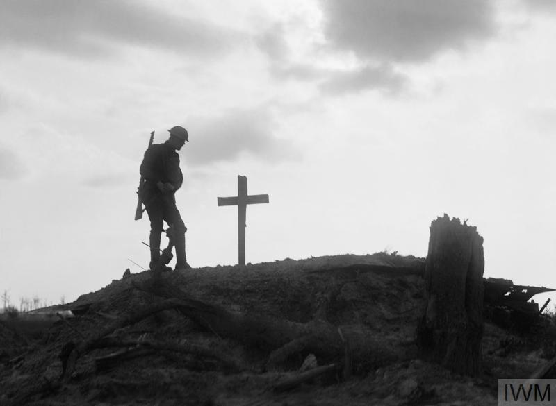 A British soldier stands besides the grave of a comrade near Pilckem during the Third Battle of Ypres, 22nd August 1917.