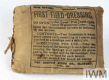 First field dressing pack in brown fabric wrapper containing two dressings and two metal safety pins, the front of the pack is printed as follows 'WAR OFFICE MEDICAL DIVISION FIRST FIELD DRESSING' and with the name of the manufacturer 'THE DARTON GIBBS CO. OLDBURY APRIL 1915'.