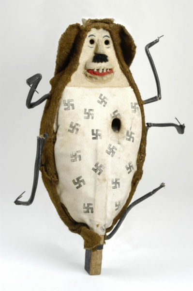 Squander Bug air rifle target mounted on a wood baton, there are numerous swastika symbols stencilled on the 'target', the bug additionally has five legs made from lead - one may be missing.