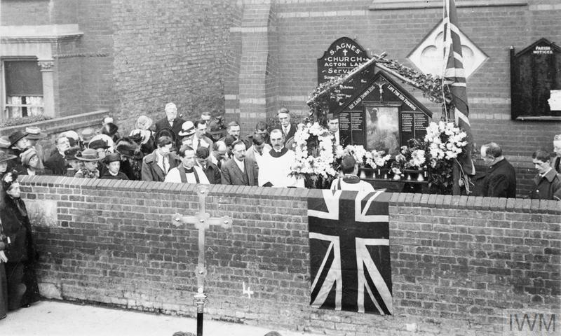 A service at a street shrine outside St Agnes' church in Acton Lane, London. Street shrines became an increasingly common expression of remembrance for the dead, particularly in working class areas, as the casualty list lengthened during and after the Battle of the Somme.