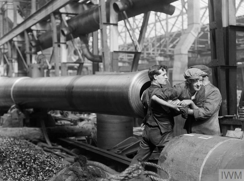 A female munitions worker is lifted into the barrel of a 15-inch naval gun manufactured at the Ordnance Works, Coventry, during the First World War, in order to clean the rifling. September 1917.