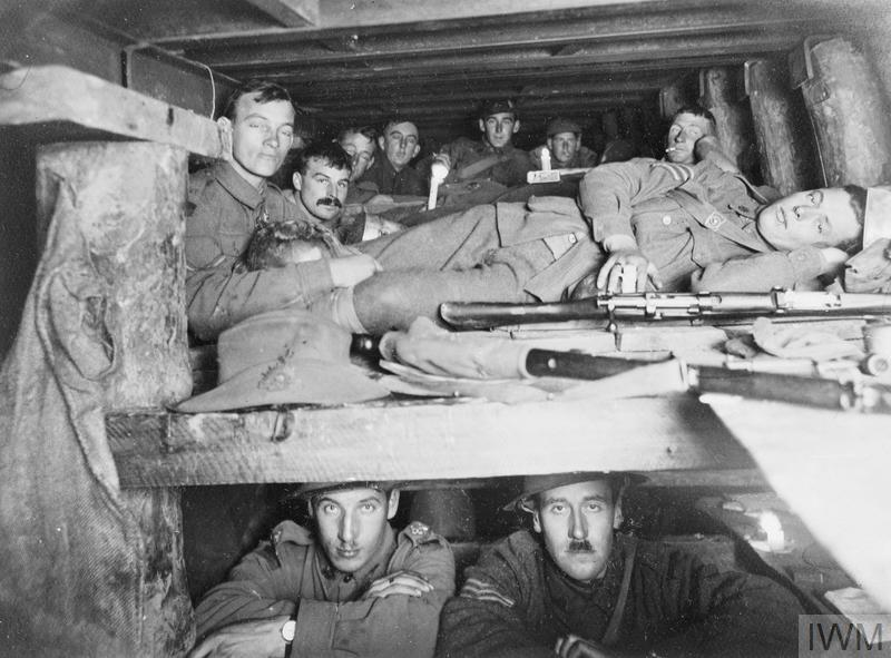 The congested interior of a dugout 15 feet below ground. Steel girders support the ceiling with heavy uprights. Men are crowded in two layers.