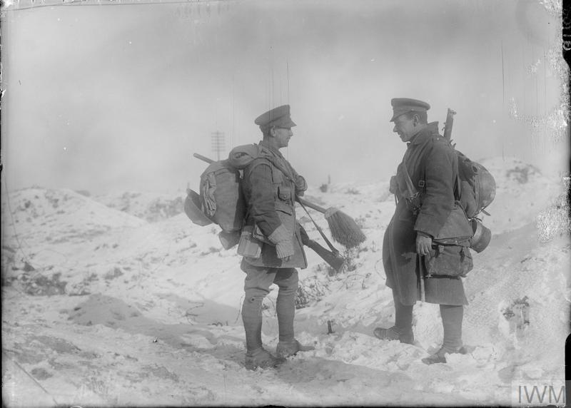 Two British soldiers carrying their rifles and equipment photographed in the snow at La Boisselle, December 1916.