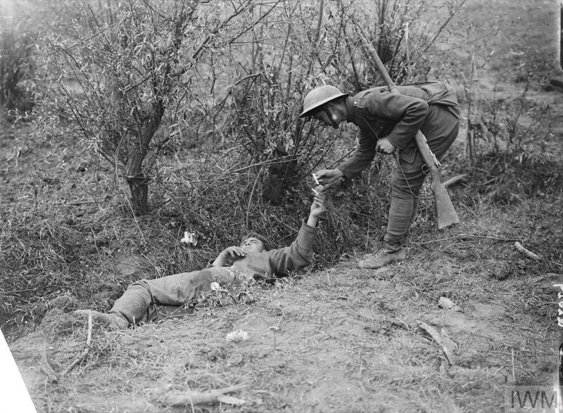The Battle of Pilckem Ridge. British soldier giving a cigarette to a badly wounded German lying in a ditch at Pilckem, 31st July 1917.