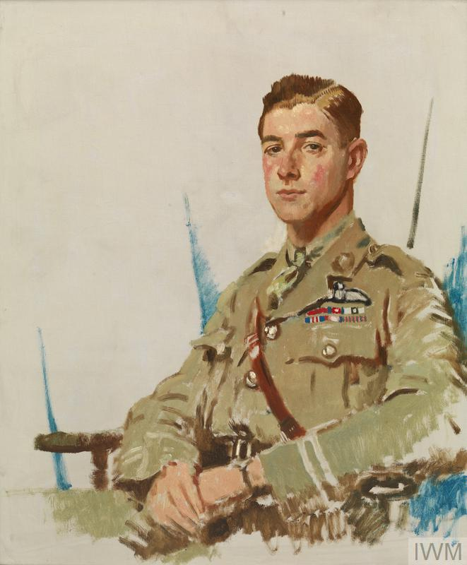 A half length portrait of McCudden in uniform sitting in a wooden armchair.