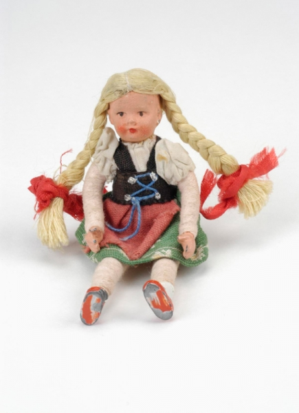Small doll dressed in traditional Austrian costume with a green flowery skirt, a white short-sleeved shirt, a blue vest and a red pinafore. The doll had long blonde hair in plaits.