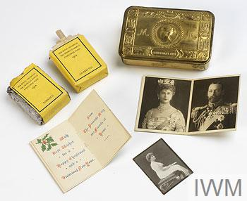Ornate brass box with contents including packet of tobacco and packet of cigarettes, a portrait photograph of Princess Mary, Christmas cards from Princess Mary and King George and Queen Mary.