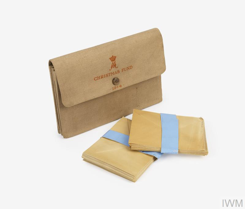 pouch, 2 packs of envelopes khaki canvas pouch (128mm x 84mm x 30mm) with single poppered flap; contains two packs of white envelopes. The flap of the pouch is adorned with a crowned M (monogram) and the text: 'CHRISTMAS FUND / 1914'.