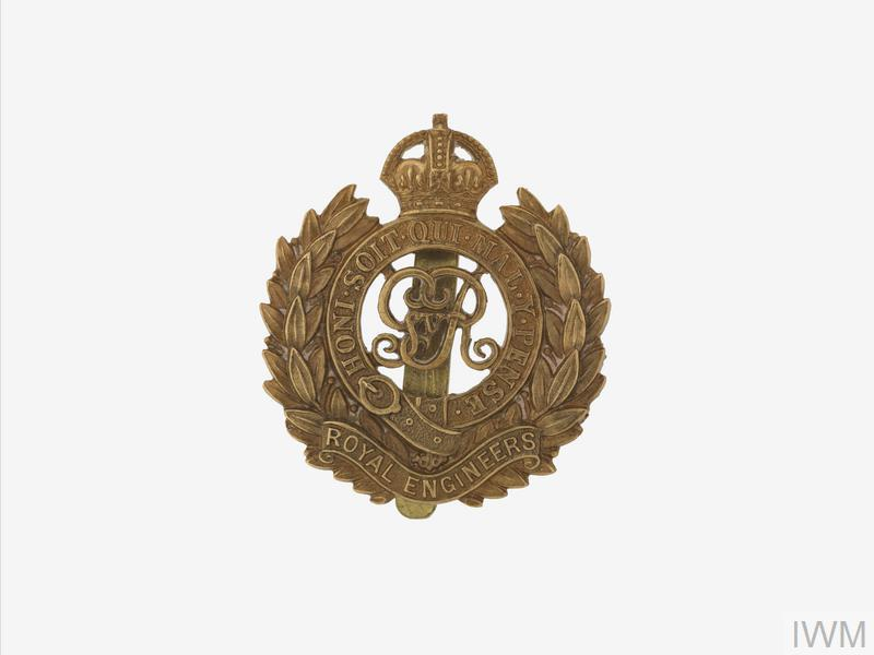 A non-voided gilt metal Royal Engineers headdress badge, the badge is shaped around the emblem which comprises GRV monogram within crowned Garter surrounded by a laurel wreath, there is a scroll below embossed with the name of the regiment 'ROYAL ENGINEERS', the badge is complete with a slider.