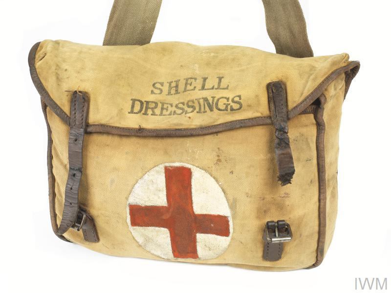 Haversack and strap: khaki canvas web haversack and shoulder strap. The haversack features a flap that is secured with two brass buckles fitted to the front face. The flap is marked (stencilled in black) 'SHELL DRESSINGS'.