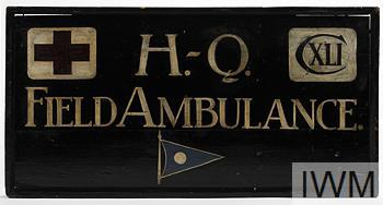 Sign: rectangular wooden sign (28in x 15in) with beaded edge, lettered in white on green ground, painted with Red Cross insignia, Roman numerals 'CXLI', 'H-Q Field Ambulance' and the emblem for 1st Infantry Division.