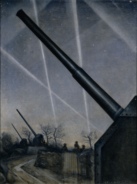 View of an anti-aircraft battery set in countryside with searchlight beams crossing the sky and attendant soldiers.