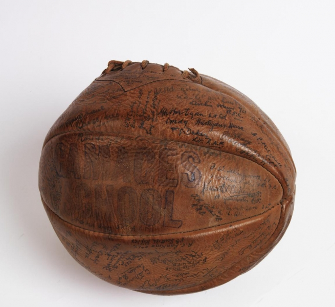 football made from eight shaped panels of brown leather stitched together. The ball bears the following handwritten inscription: 'BRITISH OFFICERS PRISONERS OF WAR CAMP. 1918. HOLZMINDEN. GERMANY. FOOTBALL CLUB SIGNATURE BALL.', which is enclosed by the signatures of Holzminden POWs.