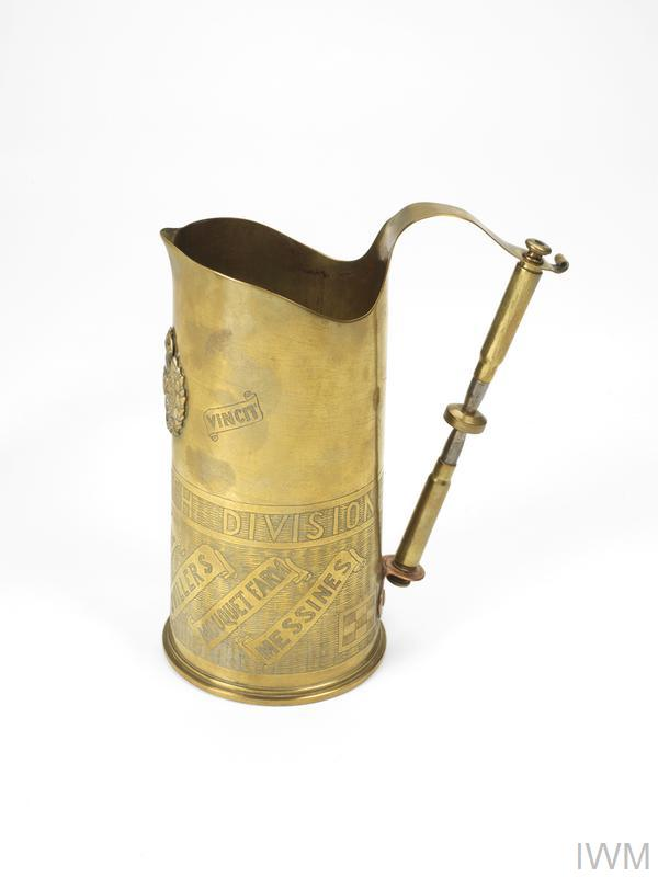 British 18-pounder Mark II brass shell case converted into a 'trench art' jug with cap badge of Royal Engineers and handle made from two 7.92mm German rifle rounds. Engraved: 'OMNIA VINCIT', 'TWENTY-FIFTH DIVISION', 'PLOEGSTEERT', 'VIMY RIDGE', 'MAILLY-MAILLET', 'THIEPVAL', 'OVILLERS', 'MOUQUET FARM', 'MESSINES'.
