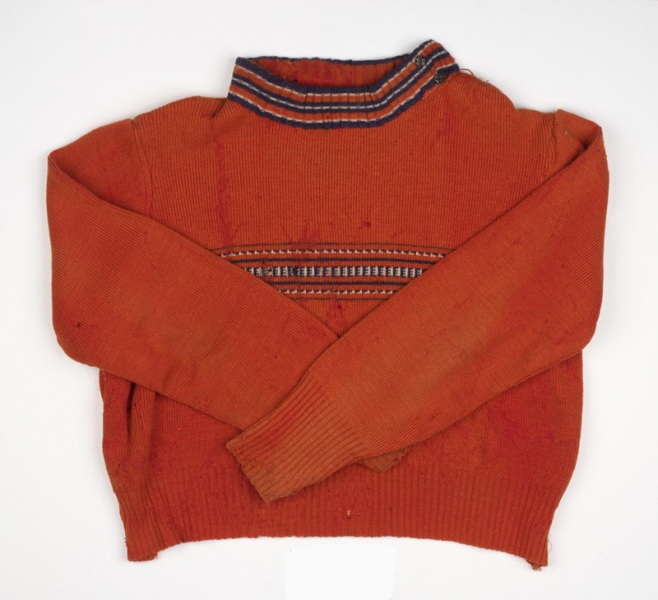 Child's red woollen jumper with blue and white decoration at the neck and across the chest. The jumper bears a number of holes.