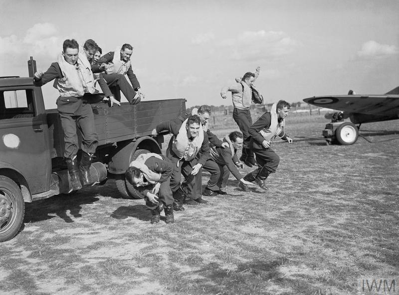 Pilots of No 19 Squadron, Royal Air Force 'scramble' for the photographer, from the back of a lorry at Fowlmere, Cambridgeshire.