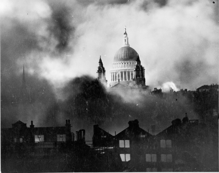 Standing out of the flames and smoke of surrounding blazing buildings, St Paul's Cathedral during the great fire raid in London.