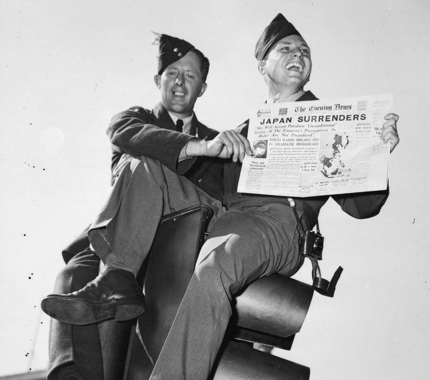 "Sergeant Franklin G Talley assisted by an RAF airman, holds up a copy of the Evening News while seated on traffic lights in Oxford Circus, London. The headline reads ""Japan Surrenders""."
