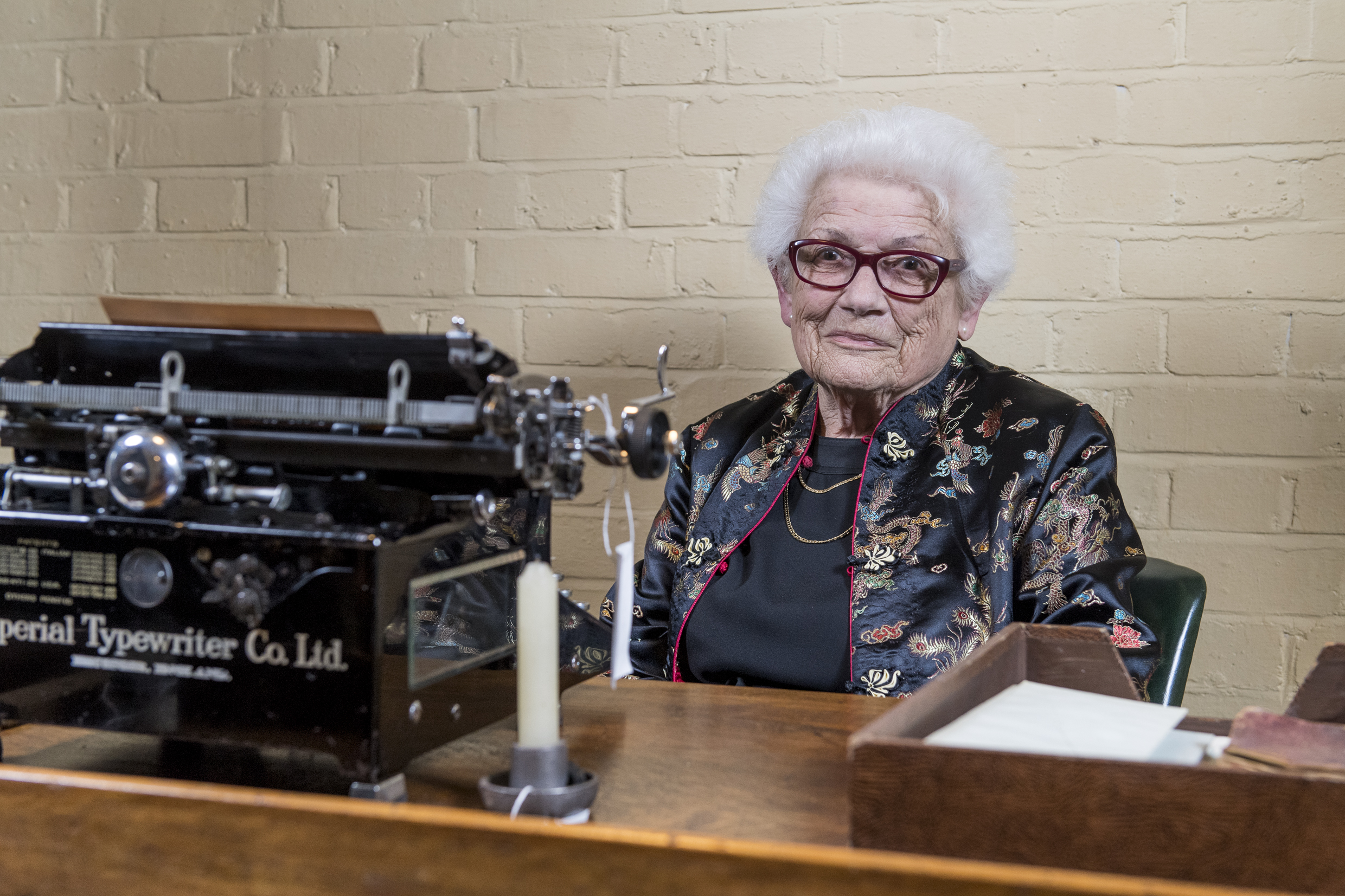 Joy Hunter, a typist in the Churchill War Rooms during the Second World War, sits behind a desk