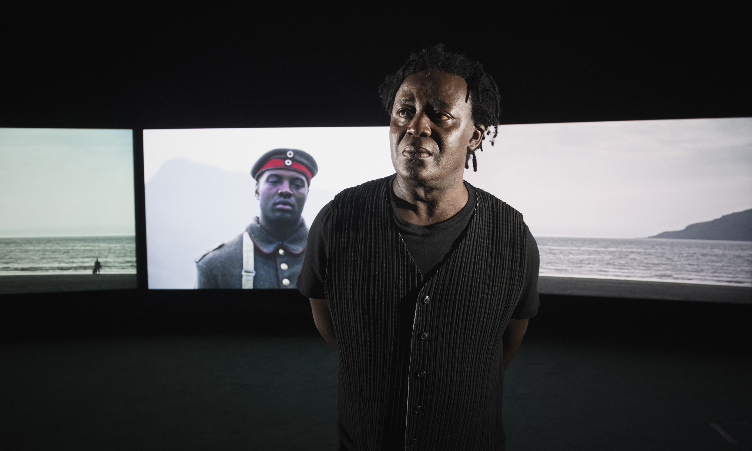 Artist John Akomfrah standing in front of his installation Mimesis: African Soldier at IWM London
