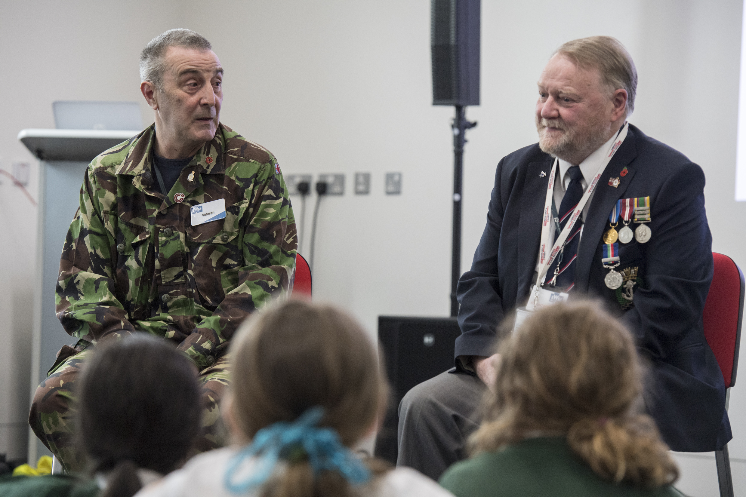 Two veterans sit on chairs in front of a group of school children